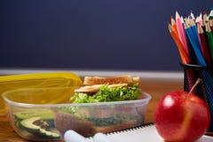 Концепция пролома школьного обеда с здоровой коробкой для завтрака и школьные принадлежности на деревянном столе, селективном фок Стоковое Изображение RF
