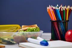 Концепция пролома школьного обеда с здоровой коробкой для завтрака и школьные принадлежности на белом столе, селективном фокусе Стоковое Изображение