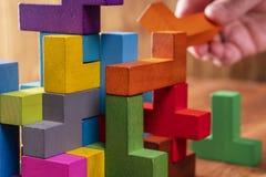 Концепция процесса принятия решения, логического мышления Рука держа деревянный элемент головоломки стоковые фото