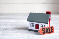 Концепция продавать дом на деревянной предпосылке стоковое изображение