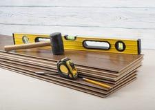 Концепция плотничества Различные инструменты выравнивают, рулетка, резиновый молоток на новом слоистом настиле Скопируйте космос  Стоковое Изображение