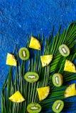 Концепция плодоовощей лета тропических Ананас, cocount и ладонь разветвляют на голубом copyspace взгляд сверху предпосылки таблиц Стоковое Изображение