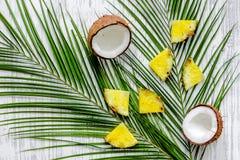 Концепция плодоовощей лета тропических Ананас, cocount и ладонь разветвляют на деревянном взгляд сверху предпосылки Стоковое Изображение RF