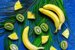 Концепция плодоовощей лета тропических Банан, киви, ананас и ладонь разветвляют на голубом взгляд сверху предпосылки таблицы Стоковые Изображения