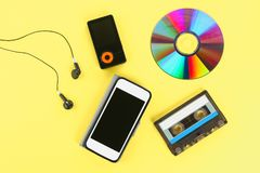 Концепция развития музыки Кассета, Компактный диск-диск, mp3 плэйер, мобильный телефон Год сбора винограда и современность Поддер стоковые изображения rf
