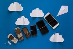 Концепция развития технологии Винтажные и новые телефоны летая на бумажный змея на голубом небе Стоковые Фотографии RF