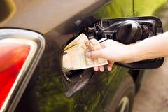 Концепция расходов транспорта - деньги евро в топливном баке автомобиля стоковые фотографии rf