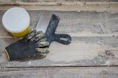 Концепция реновации и конструкции, toolings на деревянной предпосылке пола, работая перчатки, шпатель и замазка Стоковое Фото