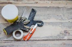 Концепция реновации и конструкции, toolings на деревянной предпосылке пола, работая перчатки, шпатель, замазка, нож и решетка Стоковые Фотографии RF