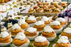 Концепция ресторанных обслуживаний: Ванильные пирожные покрыли с белой сливк, различные закуски служили на бизнес-мероприятии, го стоковое фото rf