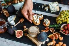 Концепция рецепта еды Тосты сыра, смокв и меда в руках в кухне Эти tartines смоквы и горгонзоли, тост, bruschetta стоковые изображения