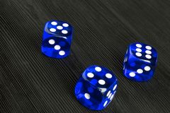 концепция риска - играть кость на черной деревянной предпосылке Играть игру с костью Голубые крены кости казино Свертывать концеп Стоковое Изображение