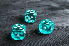 концепция риска - играть кость на черной деревянной предпосылке Играть игру с костью Голубые крены кости казино Свертывать концеп Стоковое Фото