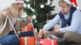 Концепция рождества и счастливого Нового Года Счастливое молодое открытие пар подарки на рождество сток-видео