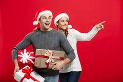 Концепция рождества - молодые привлекательные пары держа много настоящие моменты наслаждаются ходить по магазинам и отпраздновать Стоковое фото RF