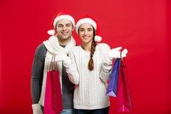 Концепция рождества - молодые привлекательные пары держа хозяйственную сумку наслаждаются ходить по магазинам и отпраздновать в Р Стоковое фото RF