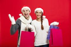 Концепция рождества - молодые привлекательные пары держа хозяйственную сумку наслаждаются ходить по магазинам и отпраздновать в Р Стоковые Изображения