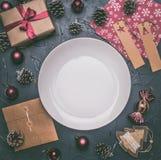 Концепция рождества, открытка, подарочная коробка, игрушки рождества и конусы, на серой предпосылке, выровнянной вокруг белой пли стоковые изображения rf