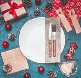 Концепция рождества, открытка, подарочная коробка, игрушки рождества и конусы, на серой предпосылке, выровнянной вокруг белой пли стоковые фото