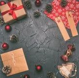 Концепция рождества, поздравительная открытка, подарочная коробка, игрушки рождества и конусы, на серой предпосылке, космос для п стоковые изображения rf