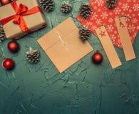 Концепция рождества, поздравительная открытка, подарочная коробка, игрушки рождества и конусы, на серой предпосылке, космос для п стоковое изображение rf
