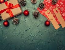 Концепция рождества, поздравительная открытка, подарочная коробка, игрушки рождества и конусы, на серой предпосылке, космос для п стоковые фотографии rf