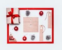 Концепция рождества, поздравительная открытка, подарочная коробка, игрушки рождества и конусы, на белой предпосылке, положение ра стоковая фотография rf