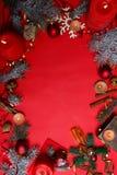 Концепция рождества, свечи, циннамон, игрушки, спрус, место для текста, на красной предпосылке Стоковые Изображения