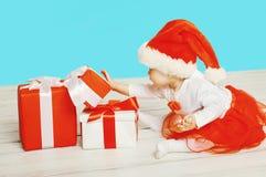 Концепция рождества - ребенок в шляпе santa красной играя с подарки коробок стоковые изображения