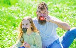 Концепция ролей рода Семья тратит отдых outdoors Папа и дочь сидят на grassplot, траве на предпосылке отец стоковые изображения