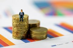 Концепция роста дела - бизнесмен сидя на стоге монетки стоковая фотография