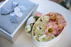 Концепция свадьбы: Золотое ожерелье колец, жемчуга и цветки пиона на белой предпосылке таблицы Стоковые Фото