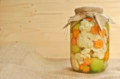 Концепция сезонного опарника солениь покрытого с дерюгой полной покрашенных зеленых сырцовых томатов, оранжевой моркови и белой ц стоковая фотография