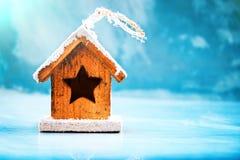 Концепция сезонных и праздников Декоративная игрушка дома на голубой предпосылке зимы льда Селективный фокус Стоковое Изображение