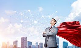 Концепция силы и успеха с супергероем бизнесмена в большом городе Стоковые Изображения RF