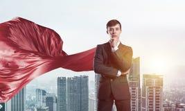Концепция силы и успеха с супергероем бизнесмена в большом городе Стоковые Фото