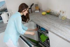 Концепция современных моя блюд, женщина вытягивает чистые блюда от судомойки в белой кухне стоковое фото
