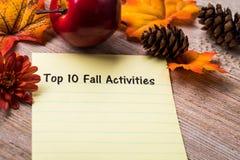 Концепция списка деятельностям при падения 10 лучших на тетради и деревянной доске Стоковые Фотографии RF