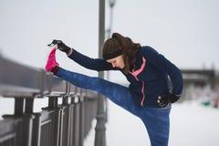 Концепция спорта - бегун модели девушки фитнеса делая тренировку гибкости для ног перед бегом на прогулке зимы снега Стоковые Изображения