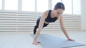 Концепция спорта и домашнего фитнеса Молодая женщина делая тренировки фитнеса в белом интерьере сток-видео