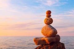 Концепция сработанности и баланса Дзэн утеса на заходе солнца Баланс и стоковая фотография
