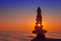 Концепция сработанности и баланса Дзэн утеса на заходе солнца Стоковые Фото