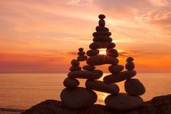 Концепция сработанности и баланса Дзэн утеса на заходе солнца стоковые фотографии rf