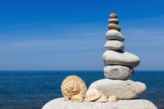 Концепция сработанности и баланса Дзэн утеса seashells на backg Стоковое Фото