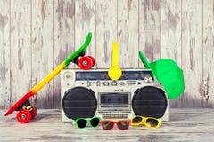 Концепция стиля хмеля музыки тазобедренного Винтажный тональнозвуковой игрок с наушниками Скейтборд, модная крышка и солнечные оч стоковые изображения
