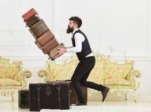Концепция страхования багажа Портер, дворецкий случайно споткнулся, падающ куча винтажных чемоданов Человек с бородой и стоковое изображение rf