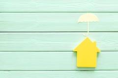Концепция страхования собственности с игрушками дома и зонтика на модель-макете взгляда сверху предпосылки мяты зеленом деревянно стоковое изображение