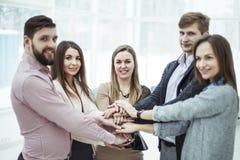 Концепция сыгранности: дружелюбная команда стоя в круге, руки дела сжиманные совместно стоковое изображение rf