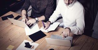 Концепция сыгранности дела 2 бородатых businessmans обсуждая идеи совместно в современном офисе Взрослый человек делая примечания Стоковые Изображения RF