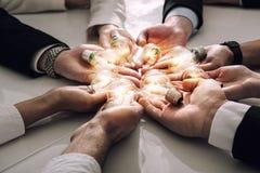Концепция сыгранности и метода мозгового штурма с бизнесменами которые делят идею с лампой Концепция запуска стоковая фотография rf